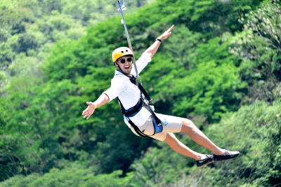 A man on the zipline with his hands spread on the air